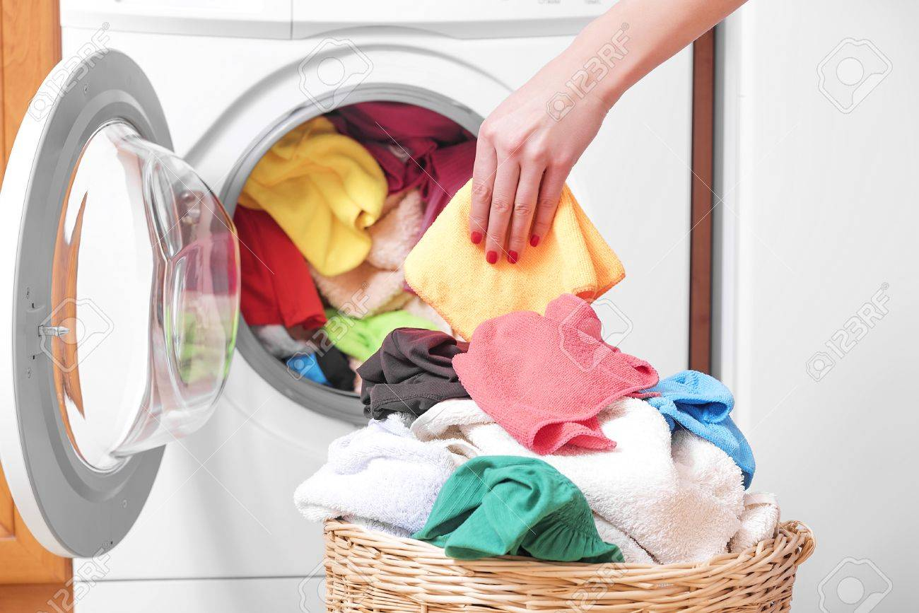 Woman loading the washing machine colored clothing. - 52746081