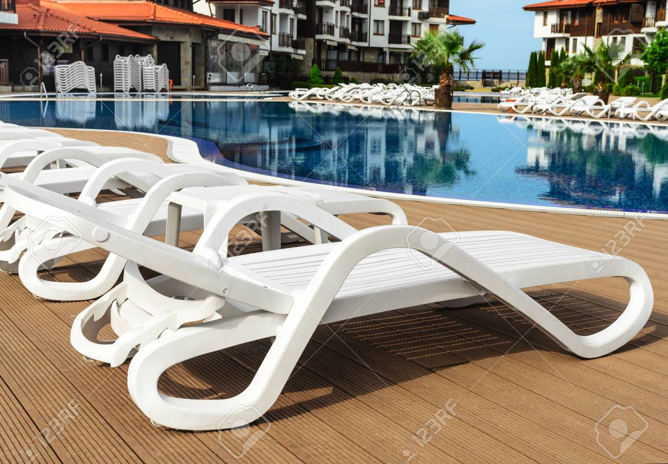 - White Plastic Chaise Lounges By The Pool. Close-up. Stock Photo