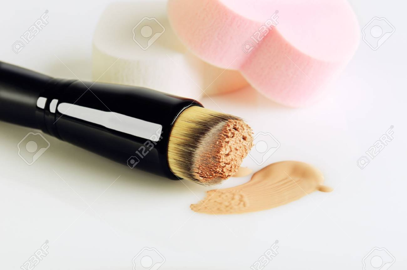 make-up brush, sponges and smear makeup base on a white background, copyspace