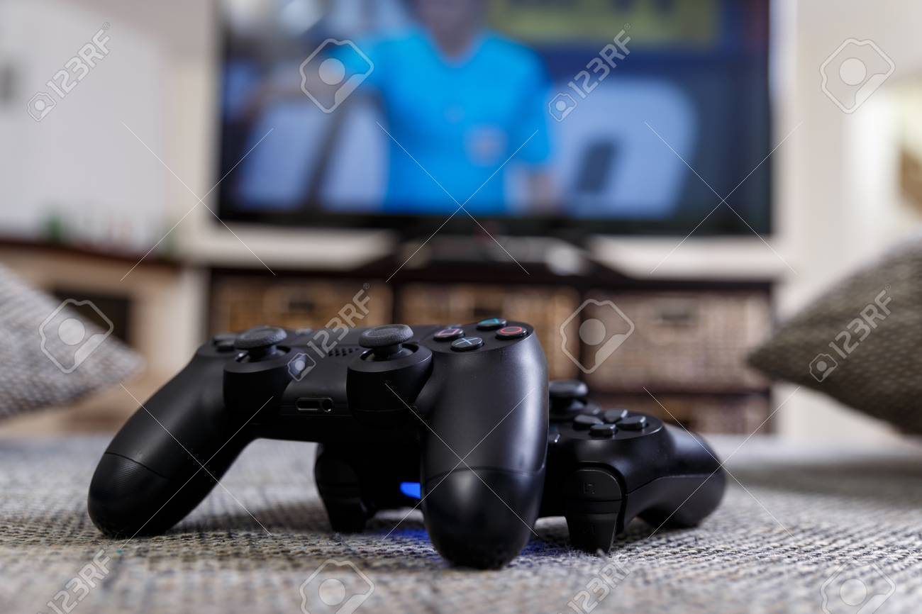 Playing Video Game Console Controllers Or Joysticks Football