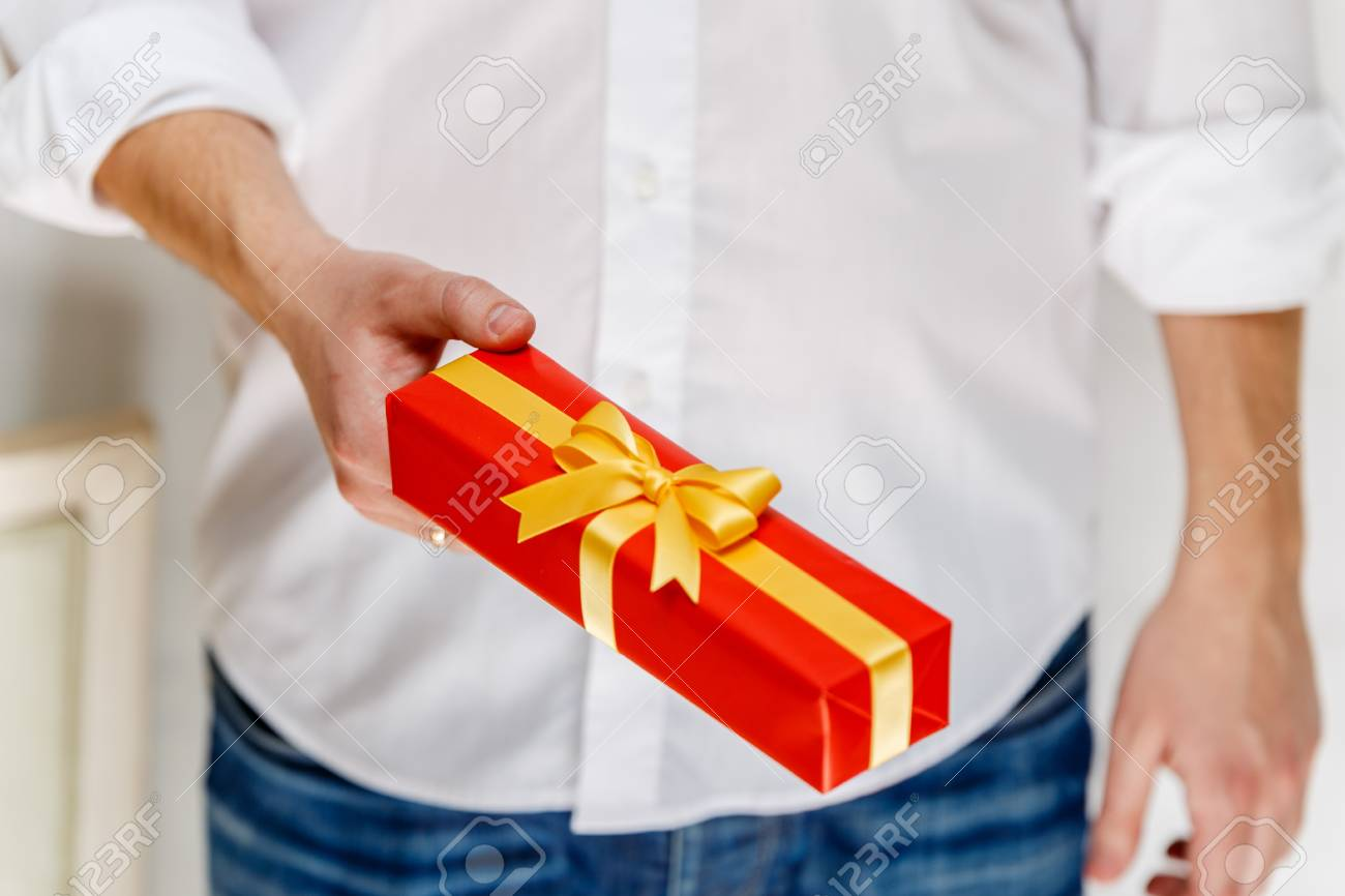 Male Hand Holding A Gift Box Present Wrapped With Ribbon And Bow Christmas Or