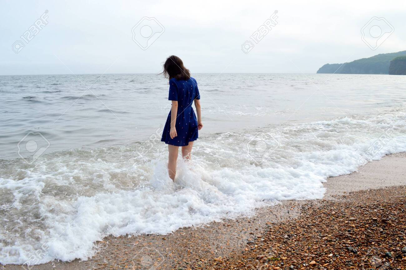 Upset thoughtful woman in blue dress going to the sea in cloudy weather before rain. She looking into the water - 146947752