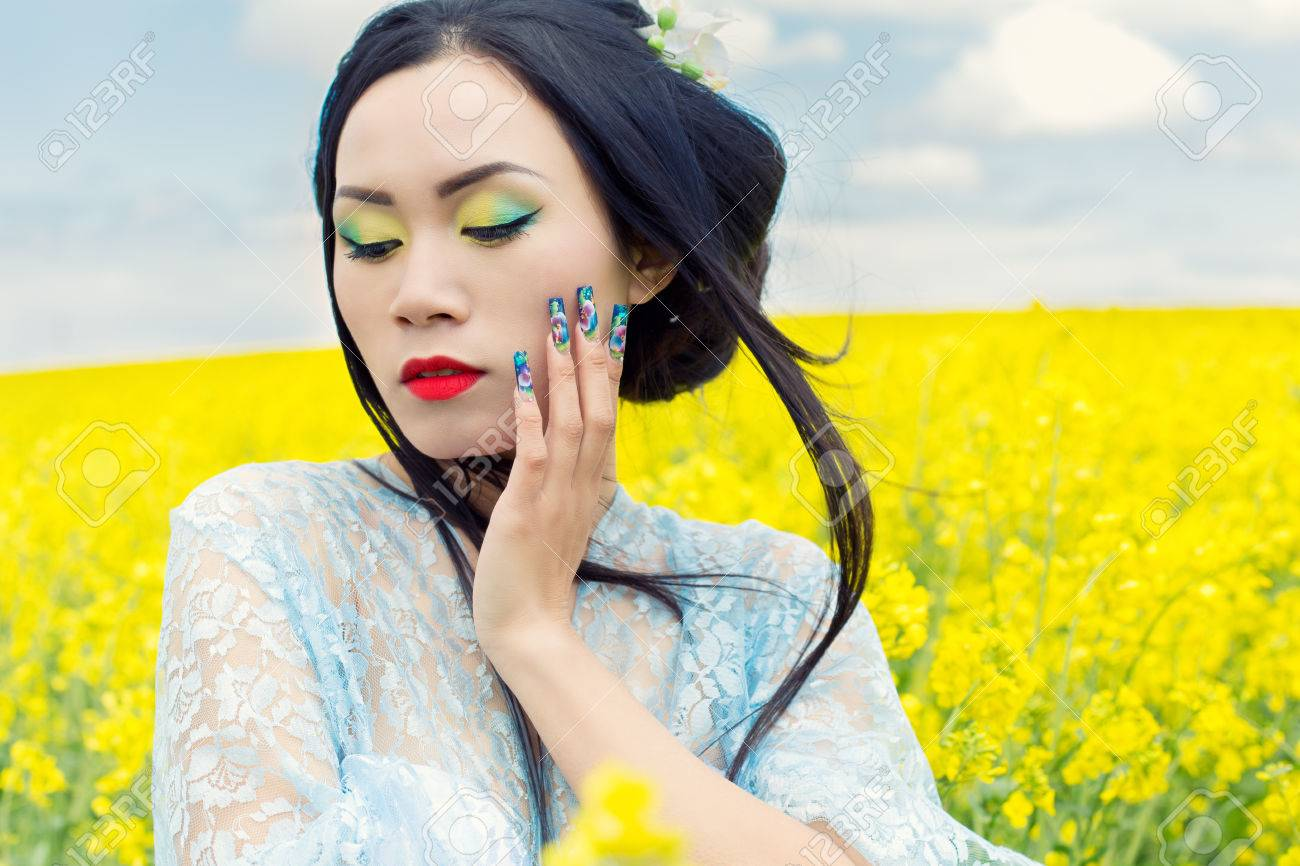Beautiful Chinese Girl In Kimono With Long False Nails With Red Lipstick In Rape Stock Photo