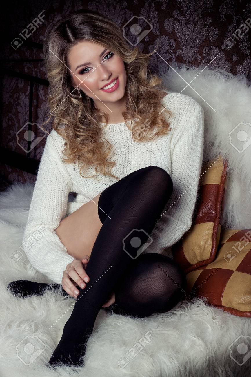 beautiful sexy sweet smiling happy girl in a warm sweater and socks is  sitting in the