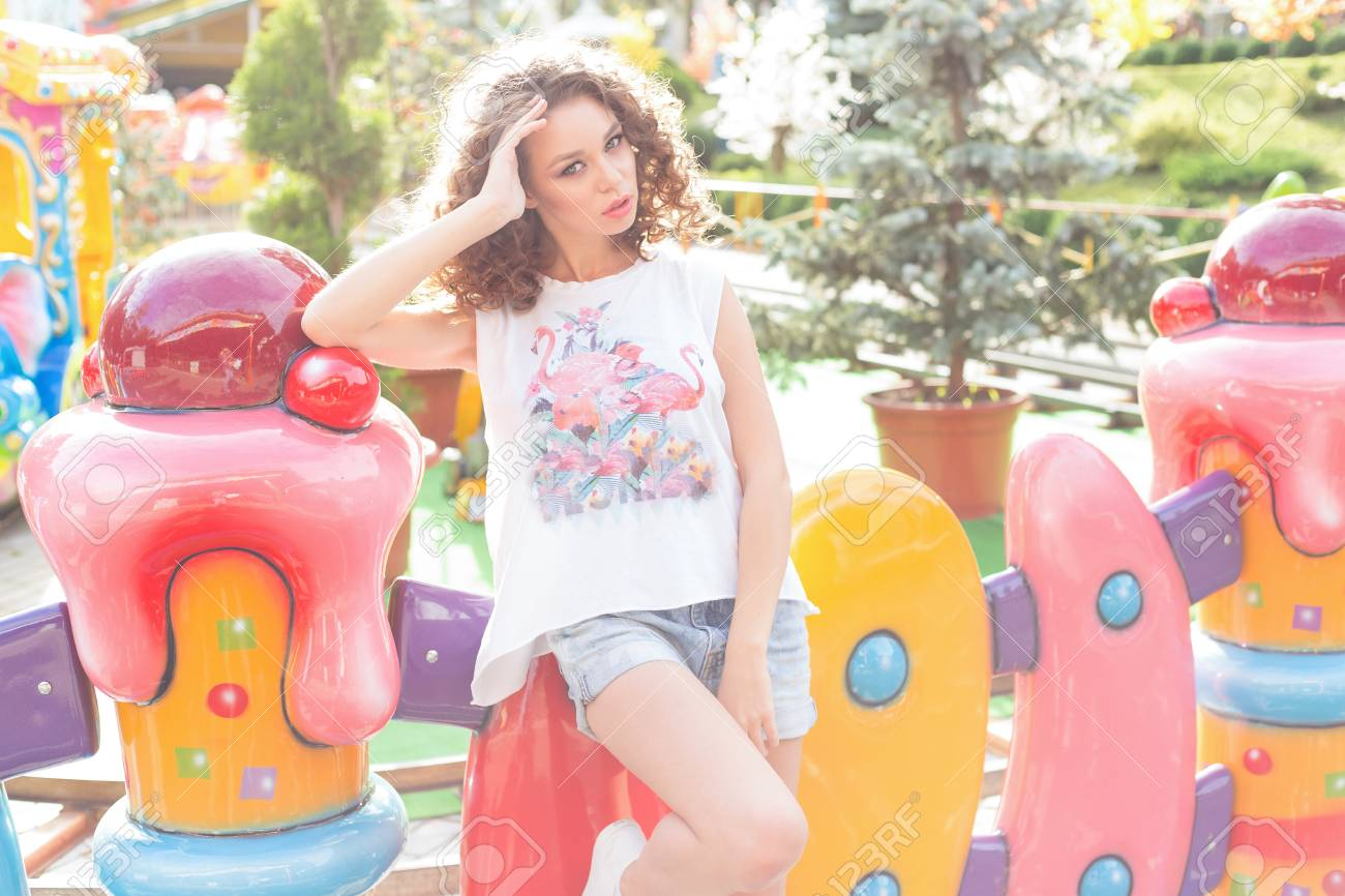 da2917b88c2791 Beautiful young cheerful girl with curly hair in denim shorts and white  T-shirt at