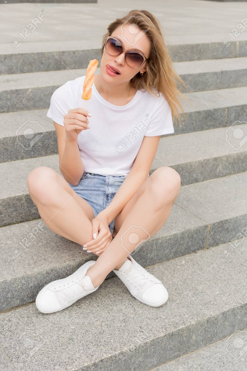 558729c196 Beautiful young sexy girl in sunglasses eating ice cream on the ladder and  licking plump lips