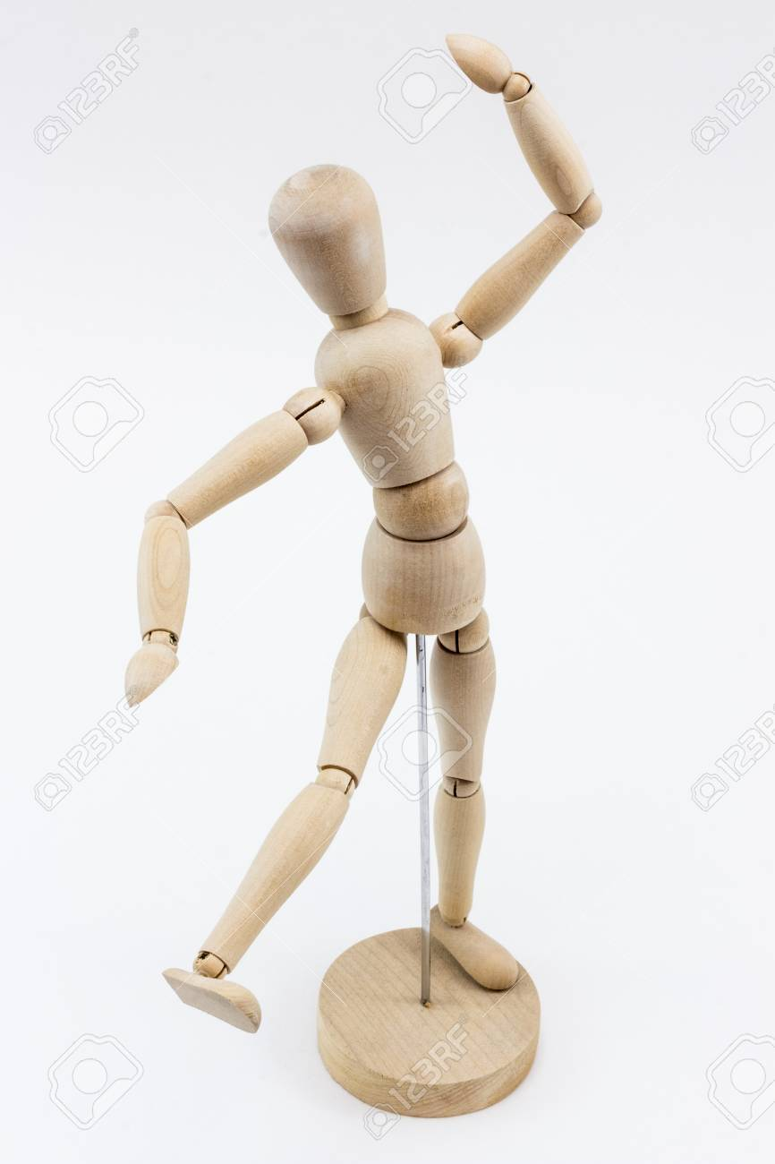 a wooden mannequin in a dance pose on it s stand on a white