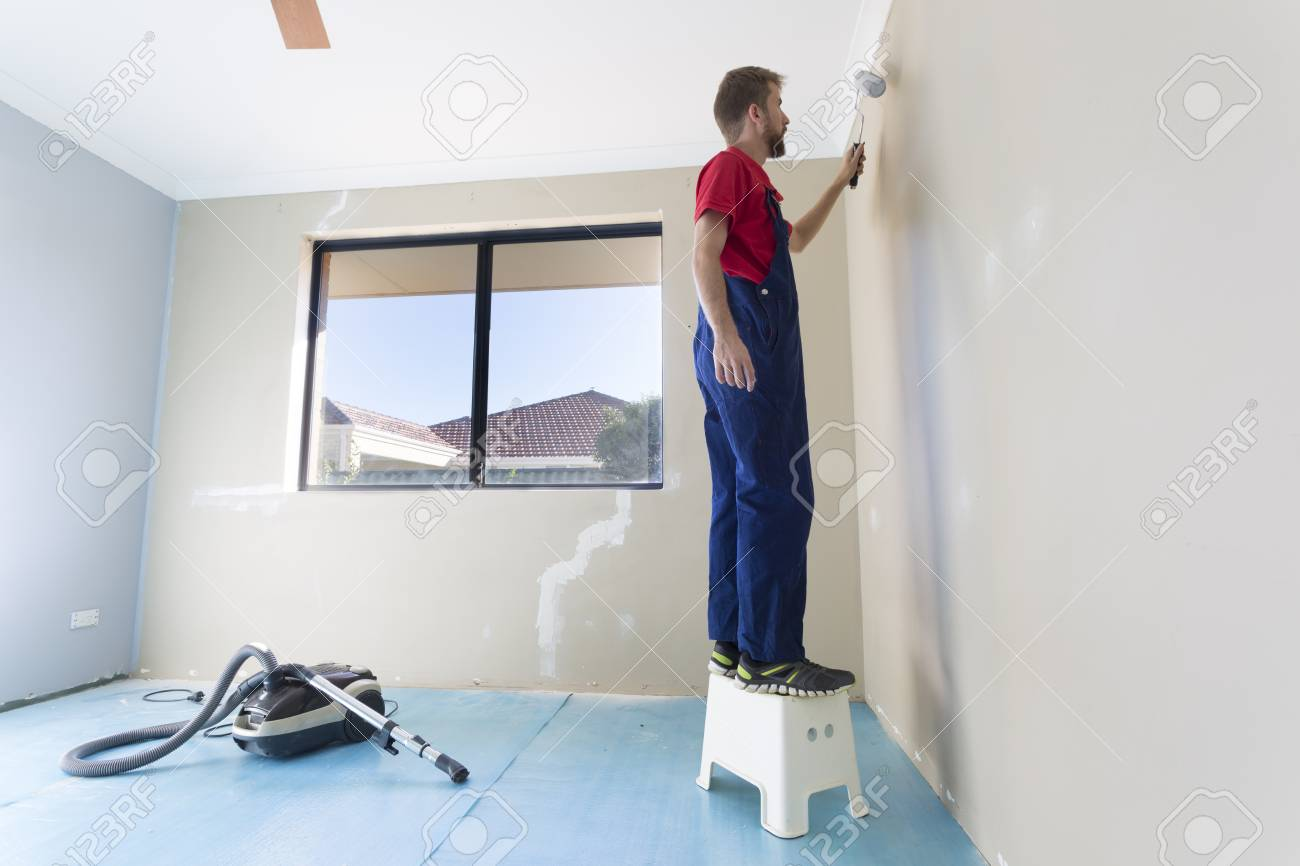 A man painting a bedroom wall.
