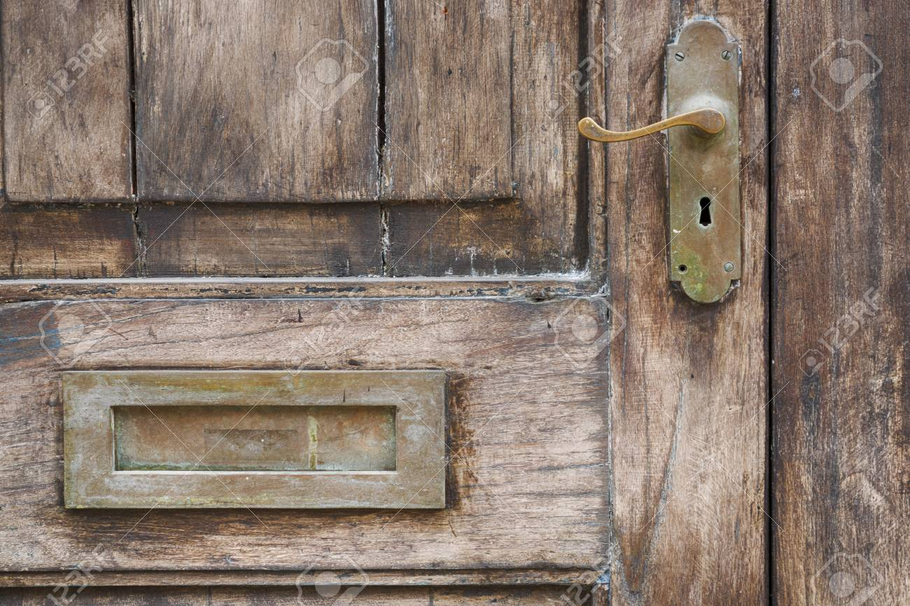 An Old Grungy Door With Antique Door Handle And Mail Slot. Stock Photo    102639205