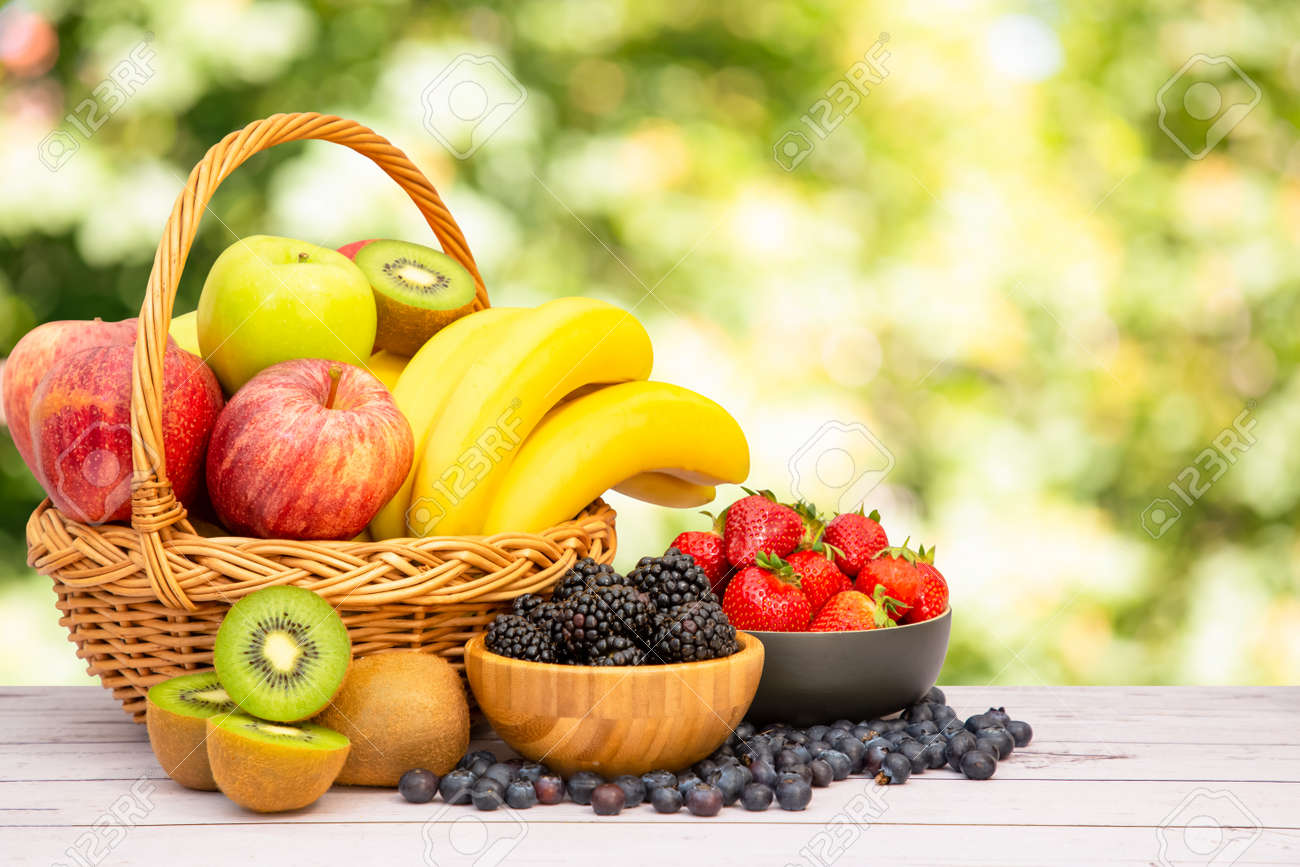 Group Healthy fresh fruit in a wooden basket, With vitamins c from bananas, kiwi, grapes, raspberries, blueberries, and blackberries, good for the body and diet food on the table in nature background. - 157319237