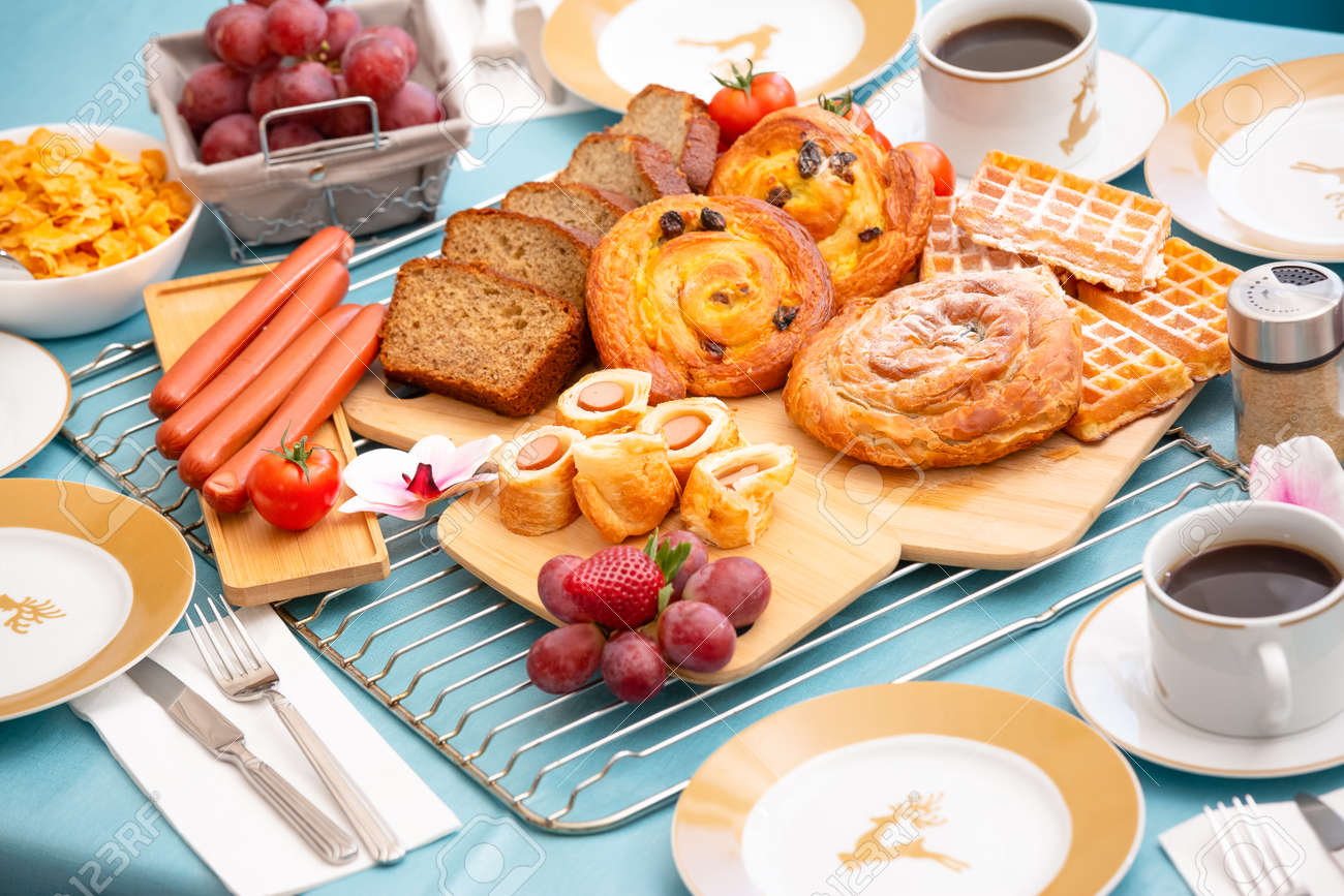 Breakfast Served in the morning with cereal bread, raisin bread, banana bread, sausage bread, chicken sausage, Natural corn flake breakfast cereal in cups and fruit on the breakfast table every day - 157501513