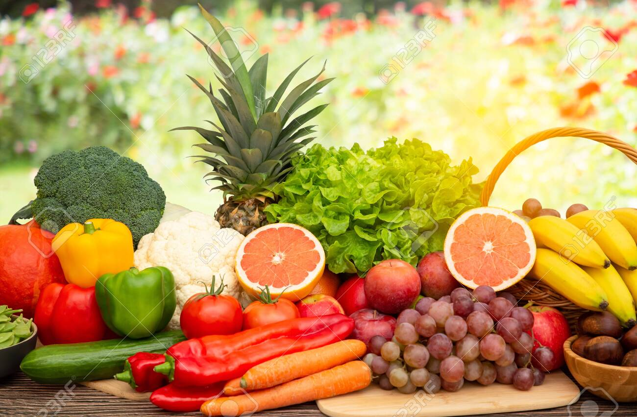 Group vegetables and Fruits Apples, grapes, oranges, and bananas in the wooden basket with carrots, tomatoes, guava, chili, eggplant, and salad on the table.Healthy food concept - 158711742