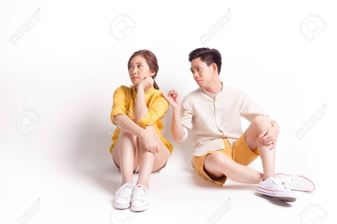 Young sulky asian female and young man trying to reconcile. sitting on white background - 119761105