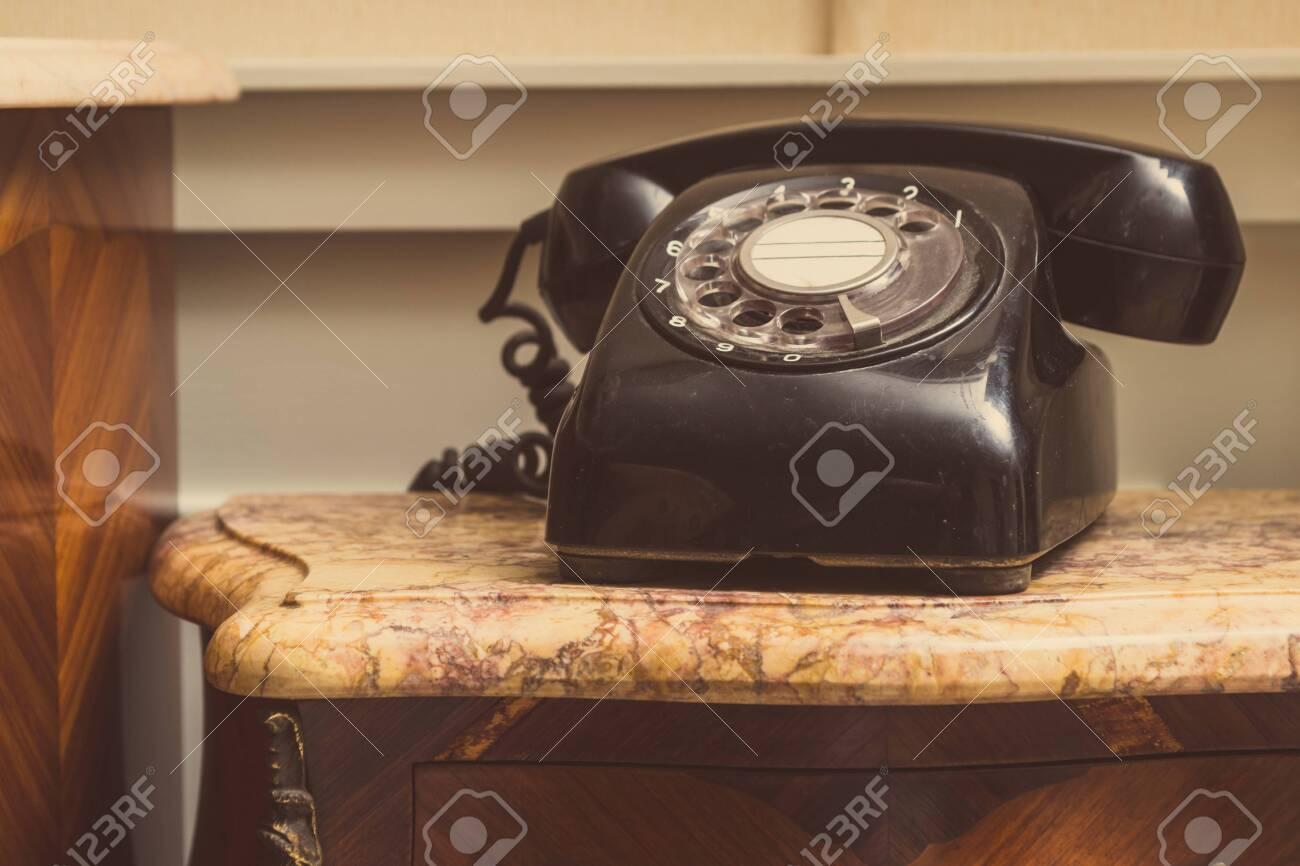 Old black telephone on stool - 148336689