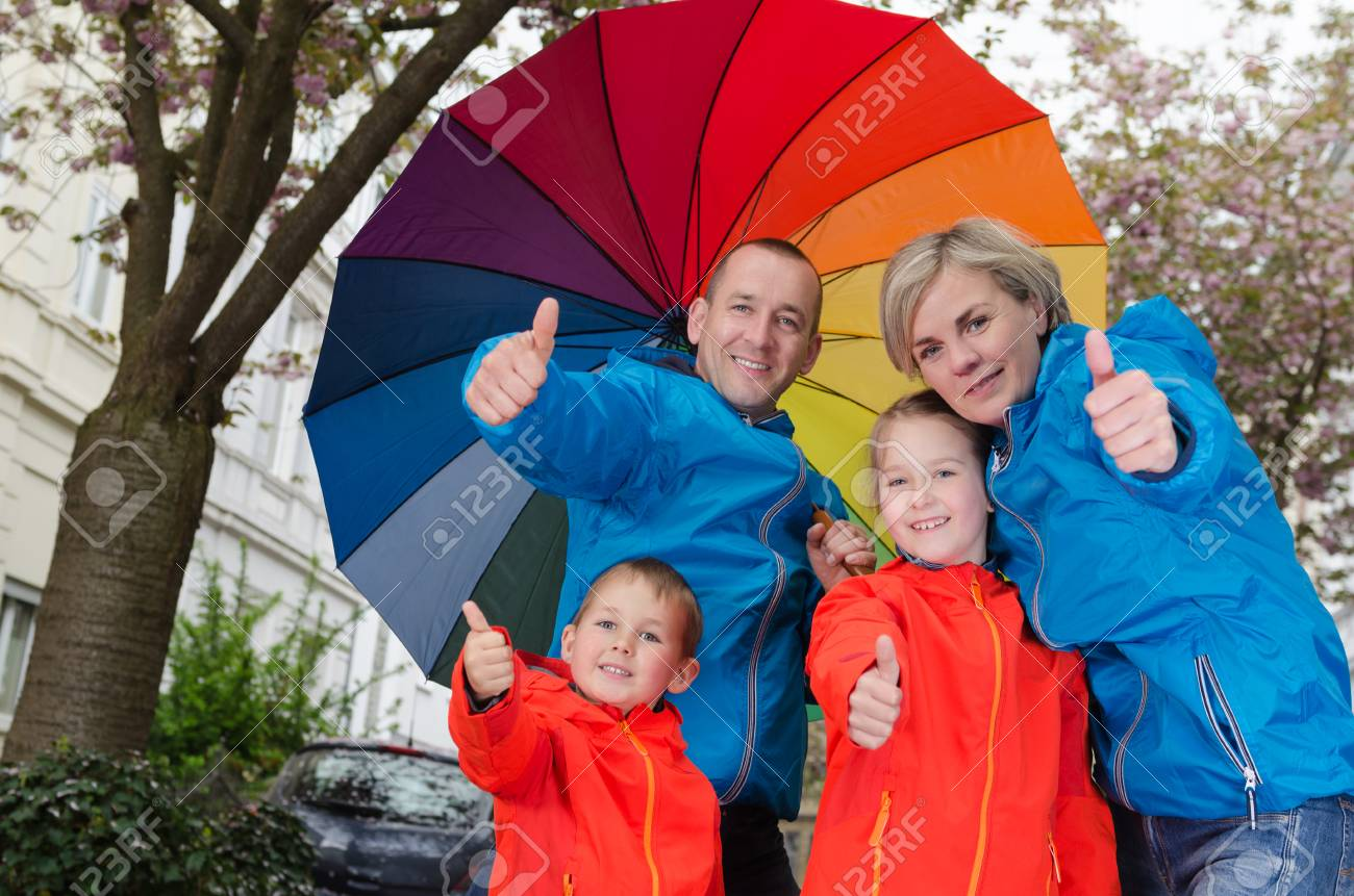 1c19a0a347f5 Happy rain family show thumbs up with umbrella