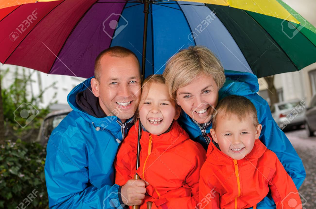 Colorful Family Smiling In The Rainy Day Under Umbrella Stock Photo ...