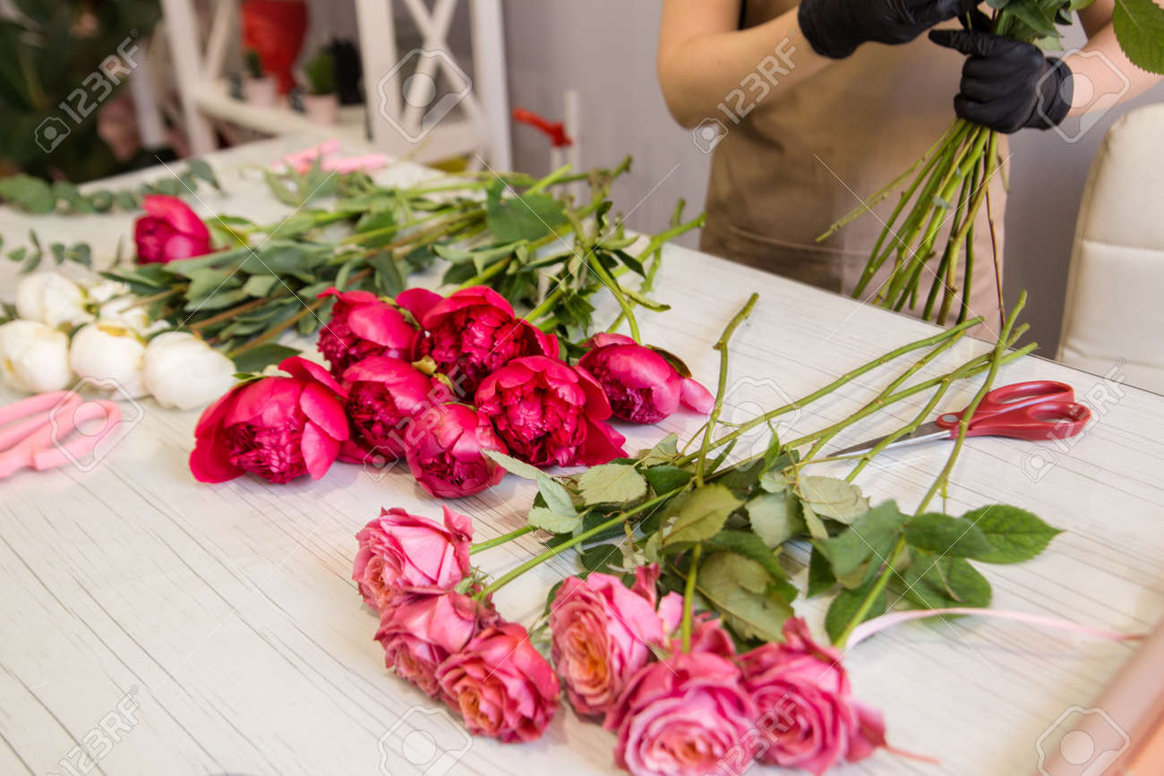 red peonies lie on the table in the flower shop - 143888173