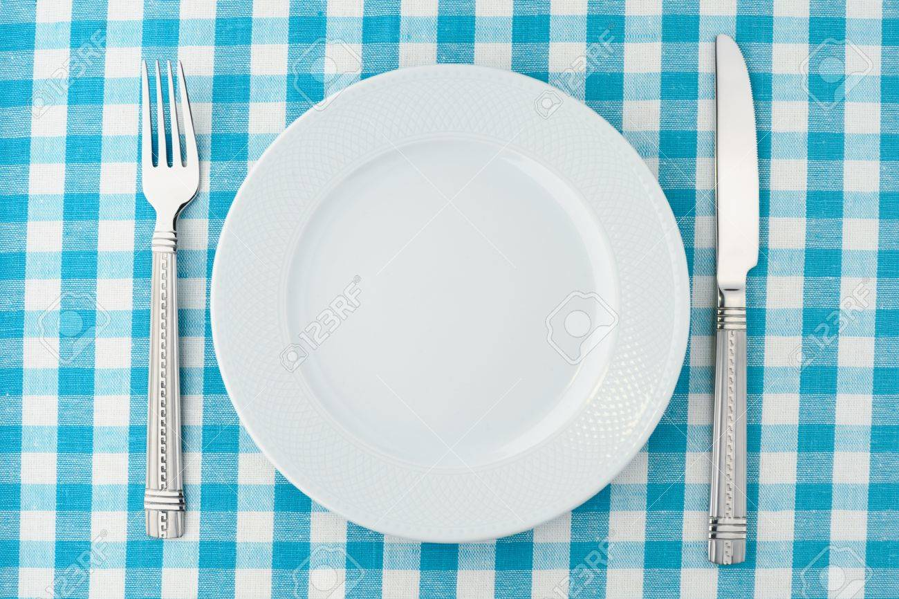 An empty white dish with knife and fork on a table - Empty Dinner Plate With Fork And Knife On Blue And White Checked Gingham Tablecloth Stock Photo