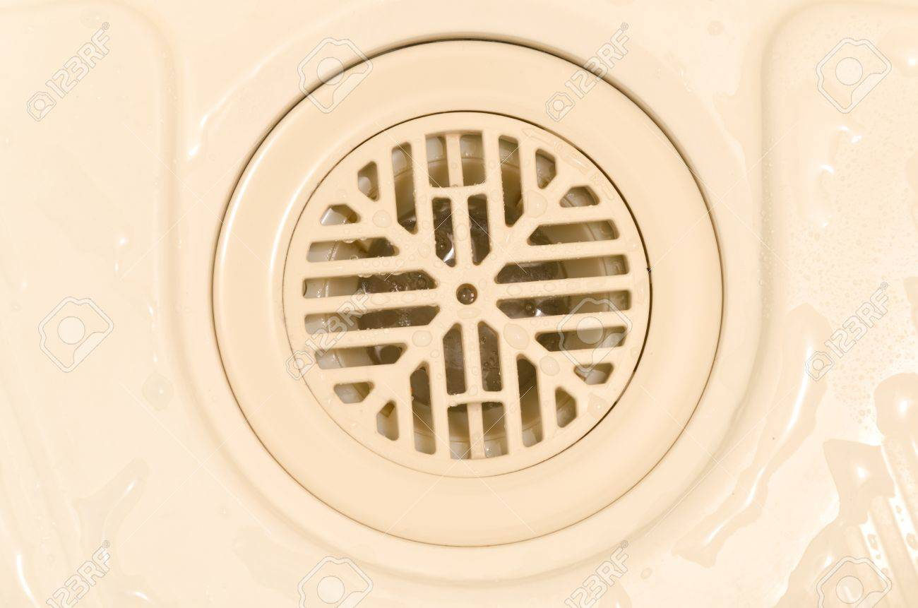 Stock Photo   Water Flow Through A Bathroom Plastic Drain Hole Cover