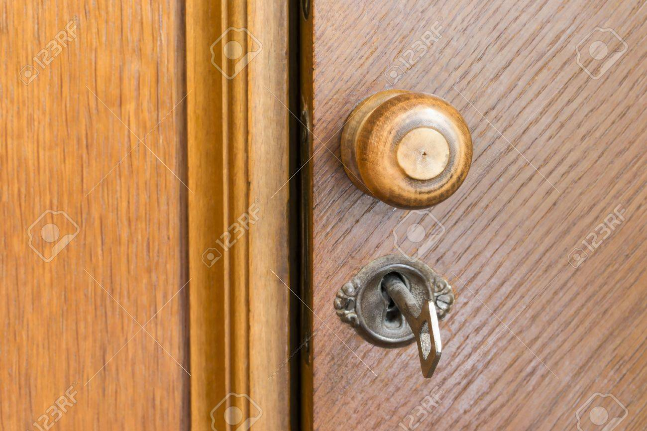 Part Of An Old Wooden Door With Round Wooden Handle And Metal Key In A  Keyhole