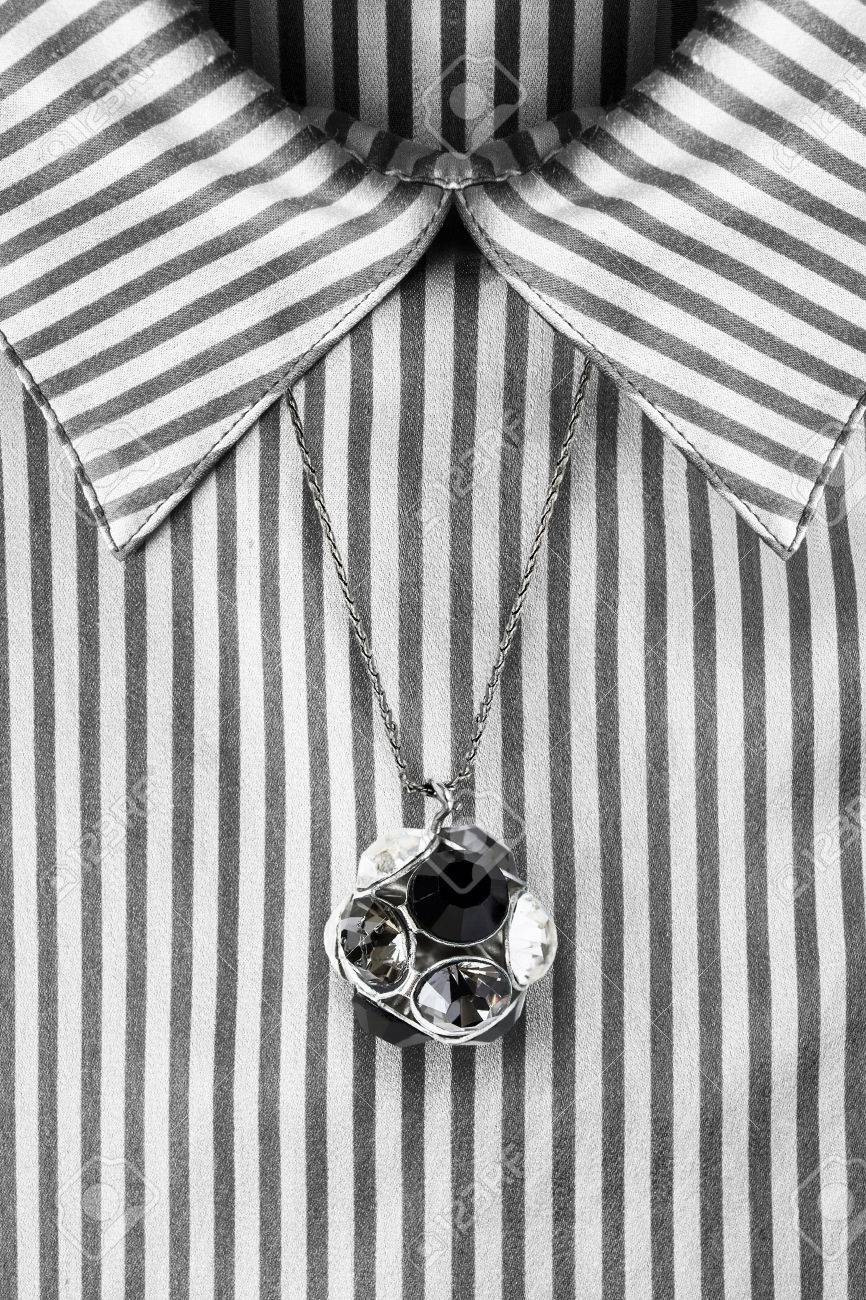 f8aa4387657576 Black and white crystal pendant over striped satin blouse closeup Stock  Photo - 77876181