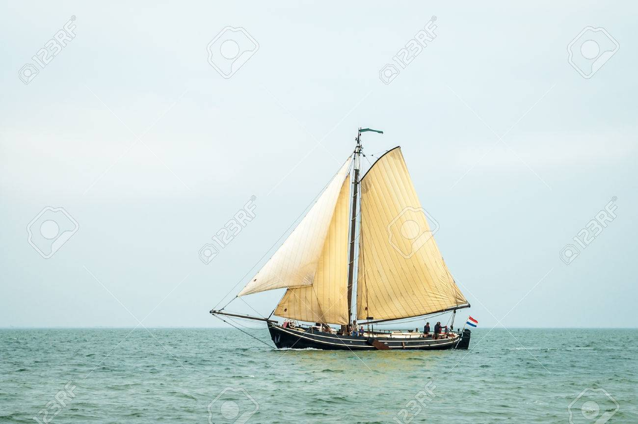 Traditional Old Dutch Wooden Sailboat Sailing On Wadden Sea