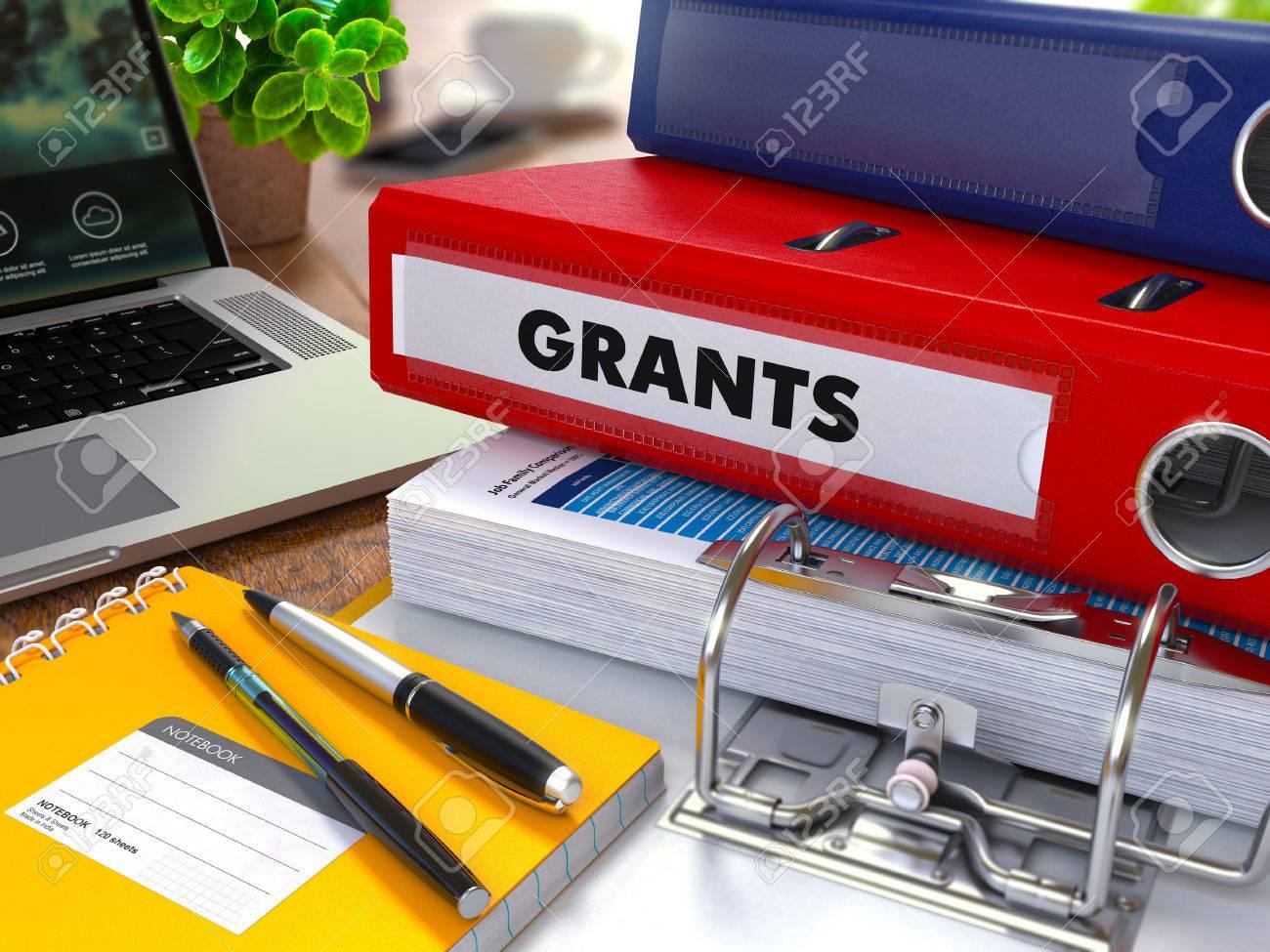 Red Ring Binder mit Beschriftung Grants auf den Hintergrund der Arbeitstisch mit Bürobedarf, Laptop, Berichte. Tonte Illustration. Business-Konzept auf unscharfen Hintergrund. Standard-Bild - 43401411