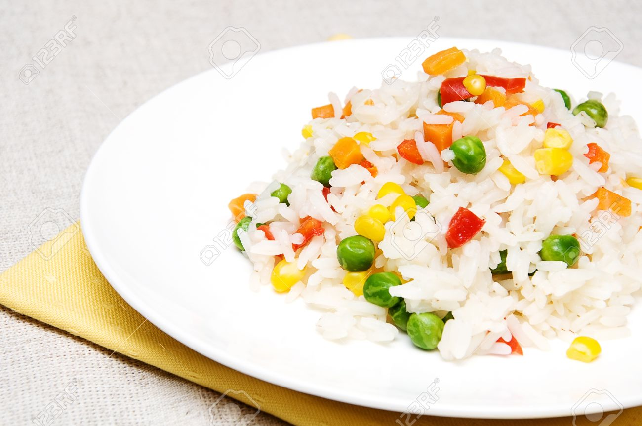 Boiled rice with green peas corn sweet peppers and carrots boiled rice with green peas corn sweet peppers and carrots on a white plate ccuart Choice Image