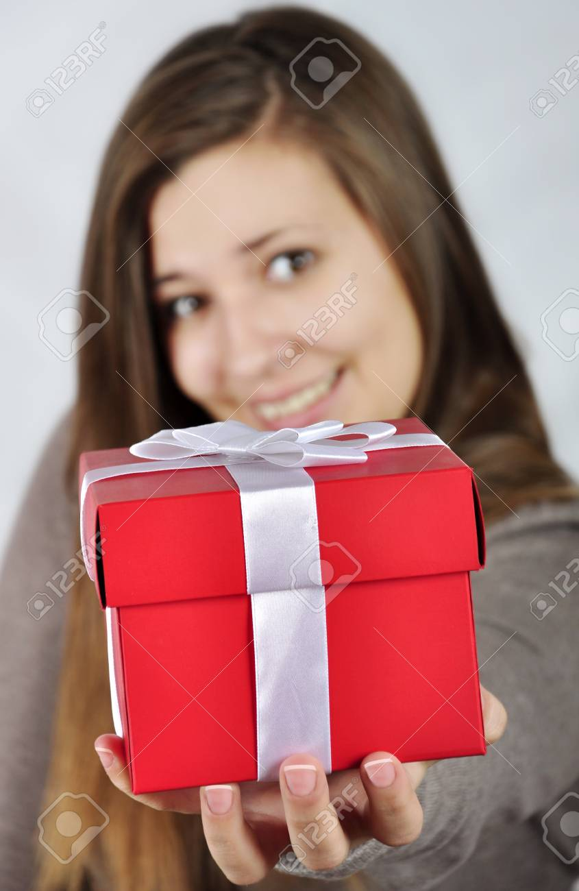 Red gift box in hand of young girl. Focus on the gift box Stock Photo - 11982322