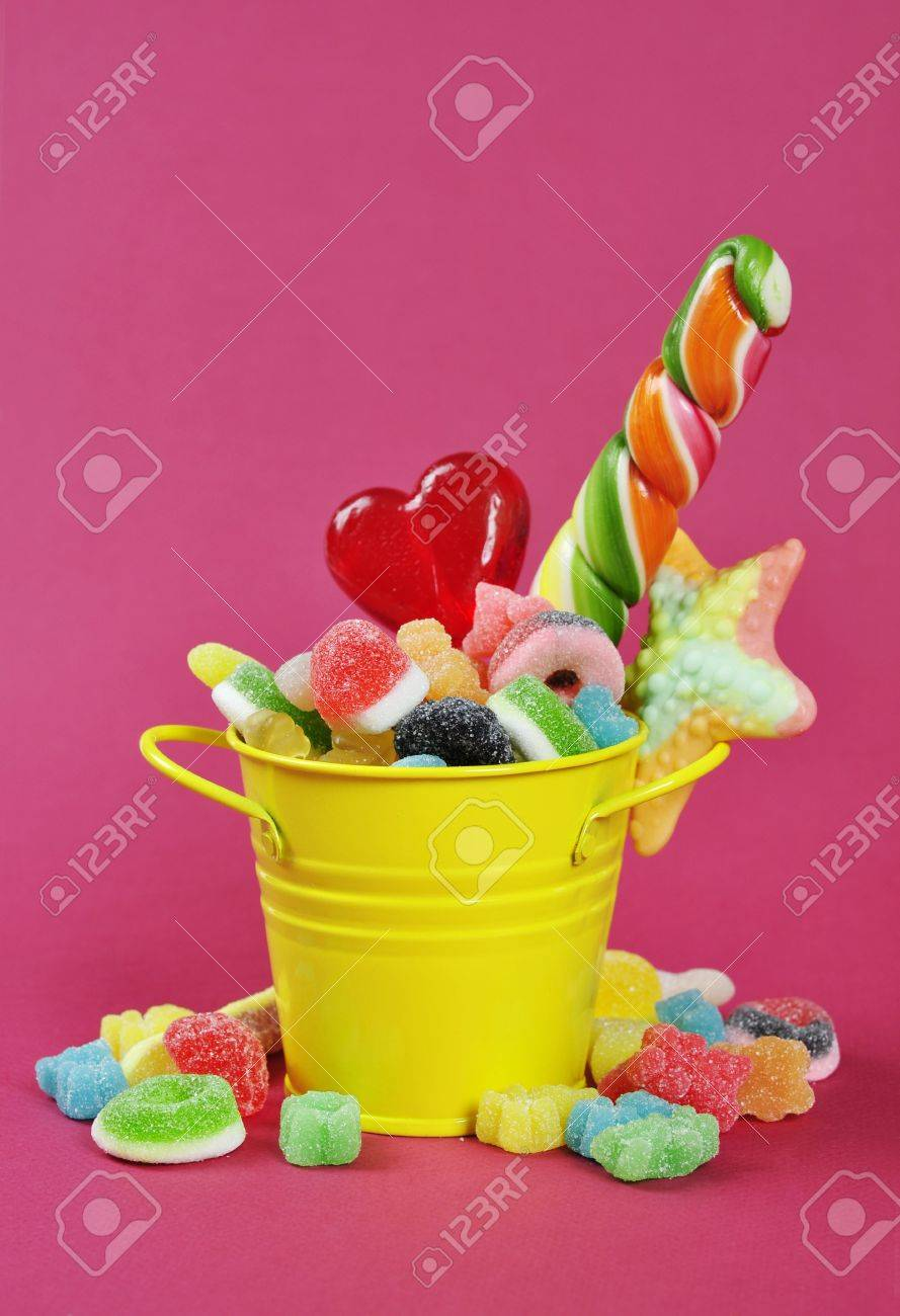 Colorful candies in yellow bucket on pink background Stock Photo - 16725091