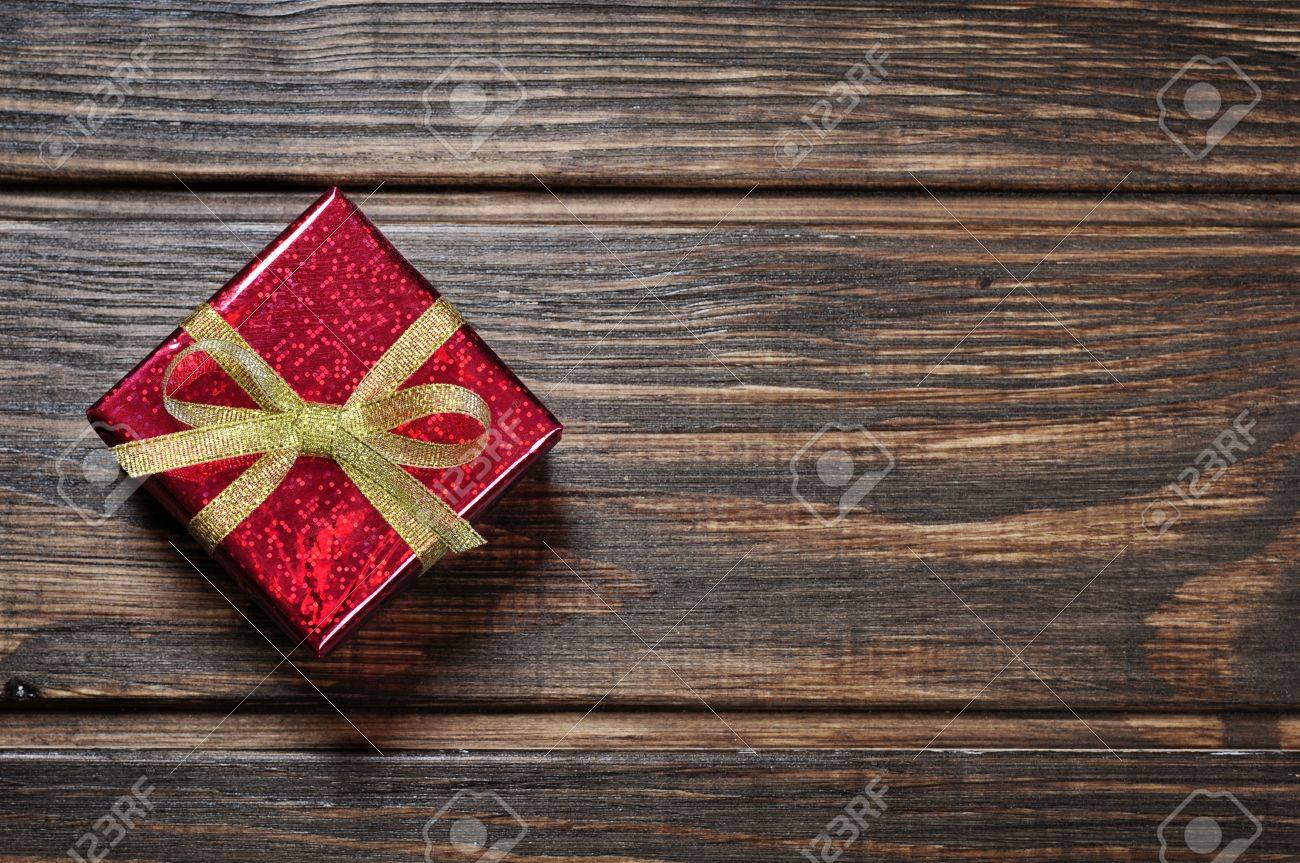 Red gift box with golden ribbon on wooden background Stock Photo - 17306522
