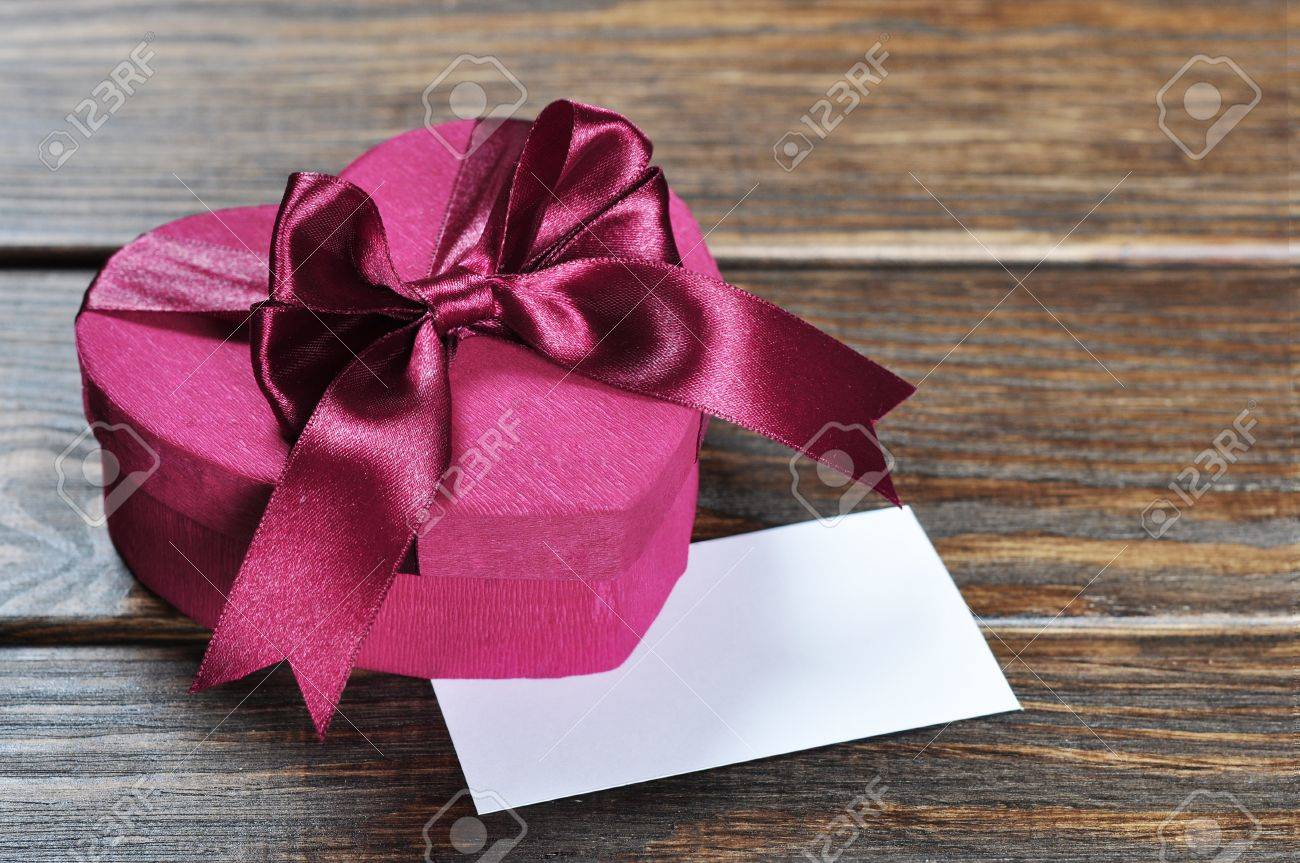 Heart shaped pink Valentines Day gift box on wooden background. Stock Photo - 17360611