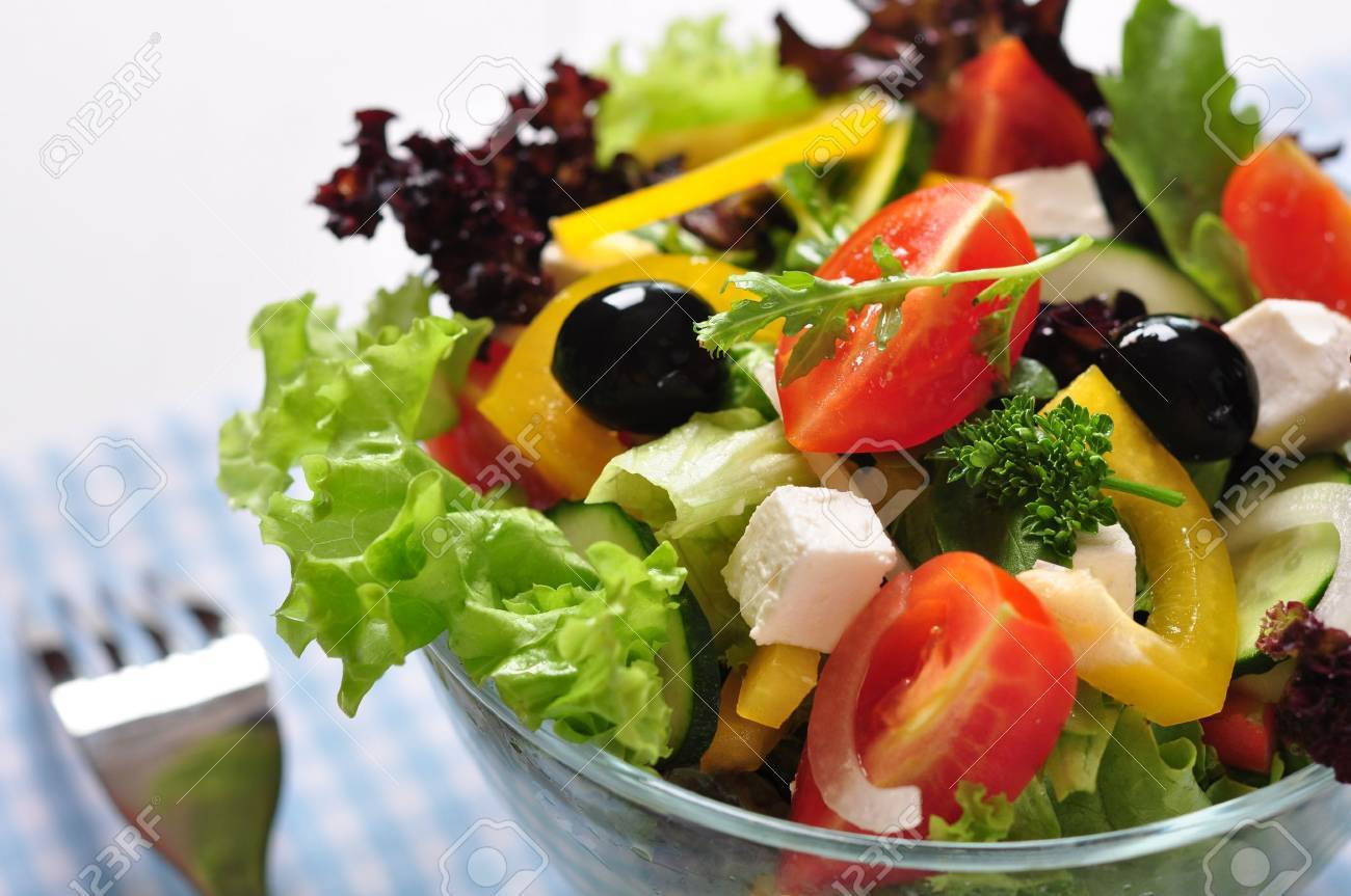 Greek salad in glass bowl on wooden background closeup - 19686098