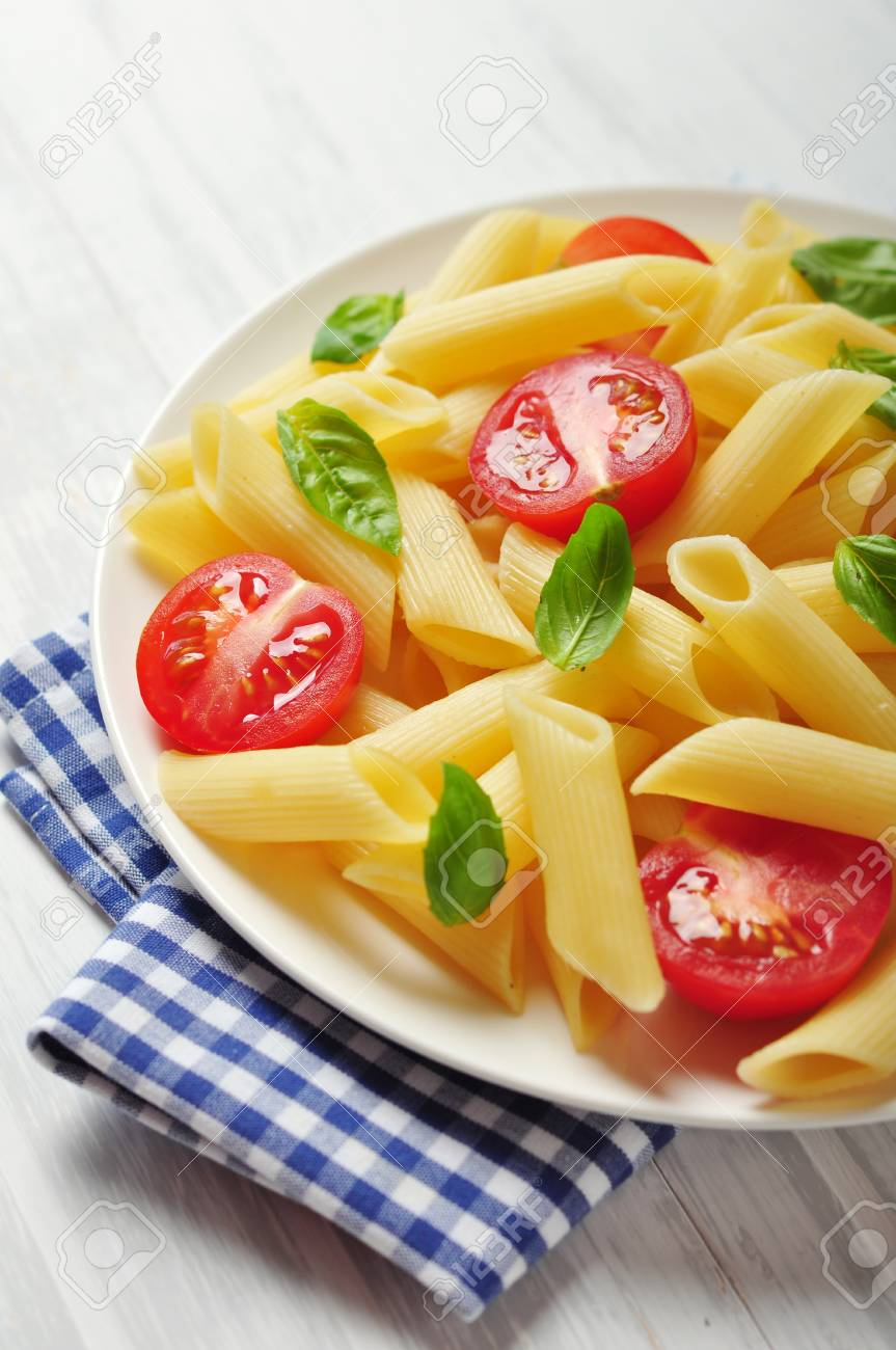 Penne pasta with cherry tomatoes and basil closeup Stock Photo - 21593965