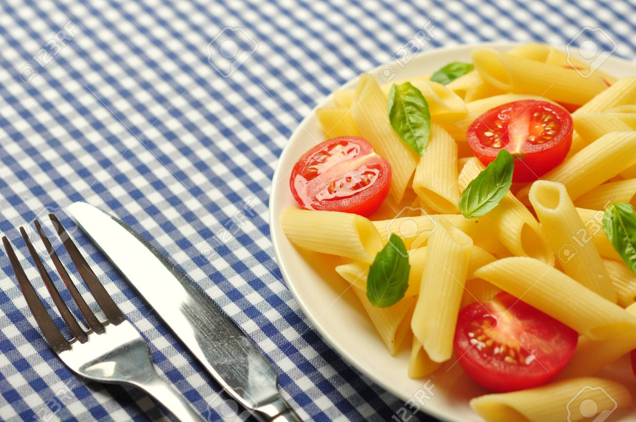 Penne pasta with cherry tomatoes and basil closeup Stock Photo - 21593967
