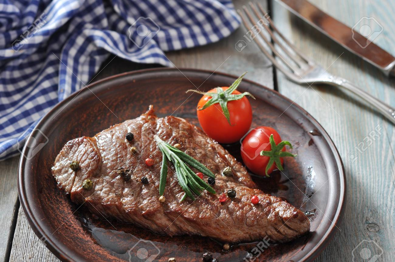 Grilled steak  on plate  with tomatoes, spices and rosemary closeup Stock Photo - 23949097