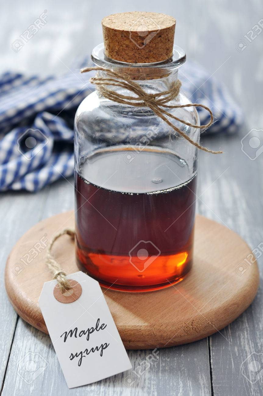f6ba9b93c34 Maple syrup in glass bottle on a wooden background Stock Photo - 26463790