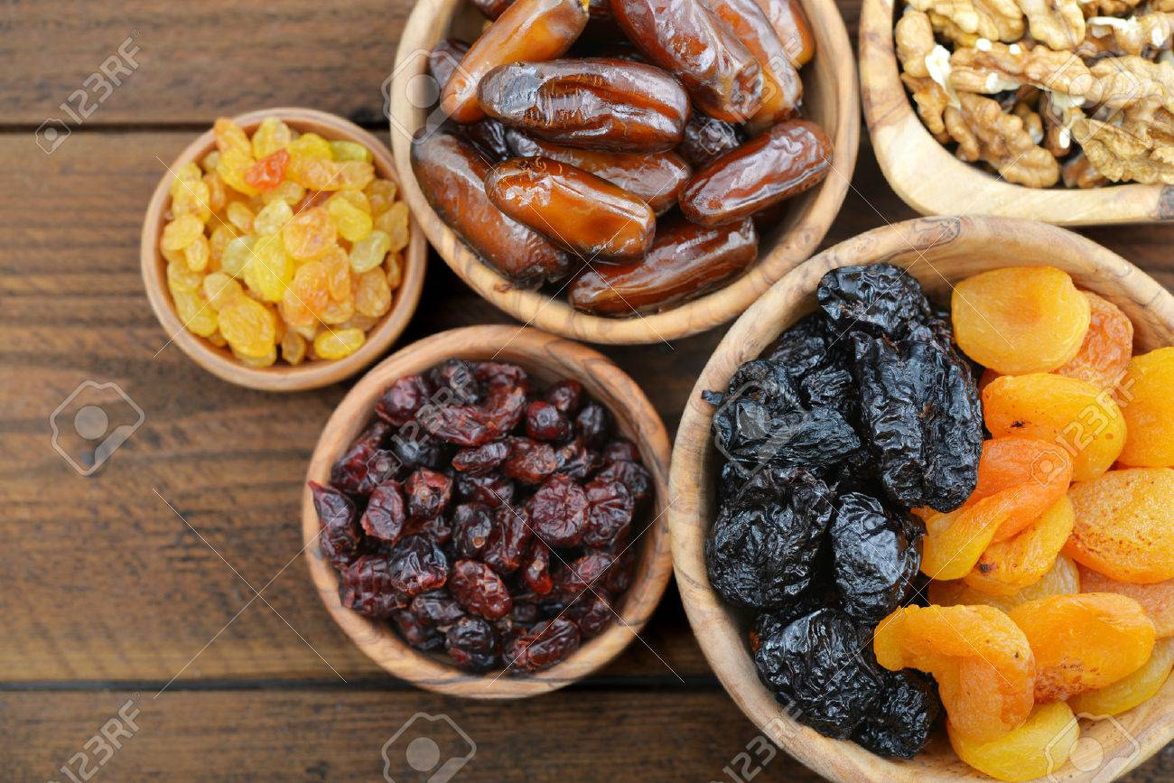 Mix of dried fruits and nuts in wooden bowls closeup - 51766400