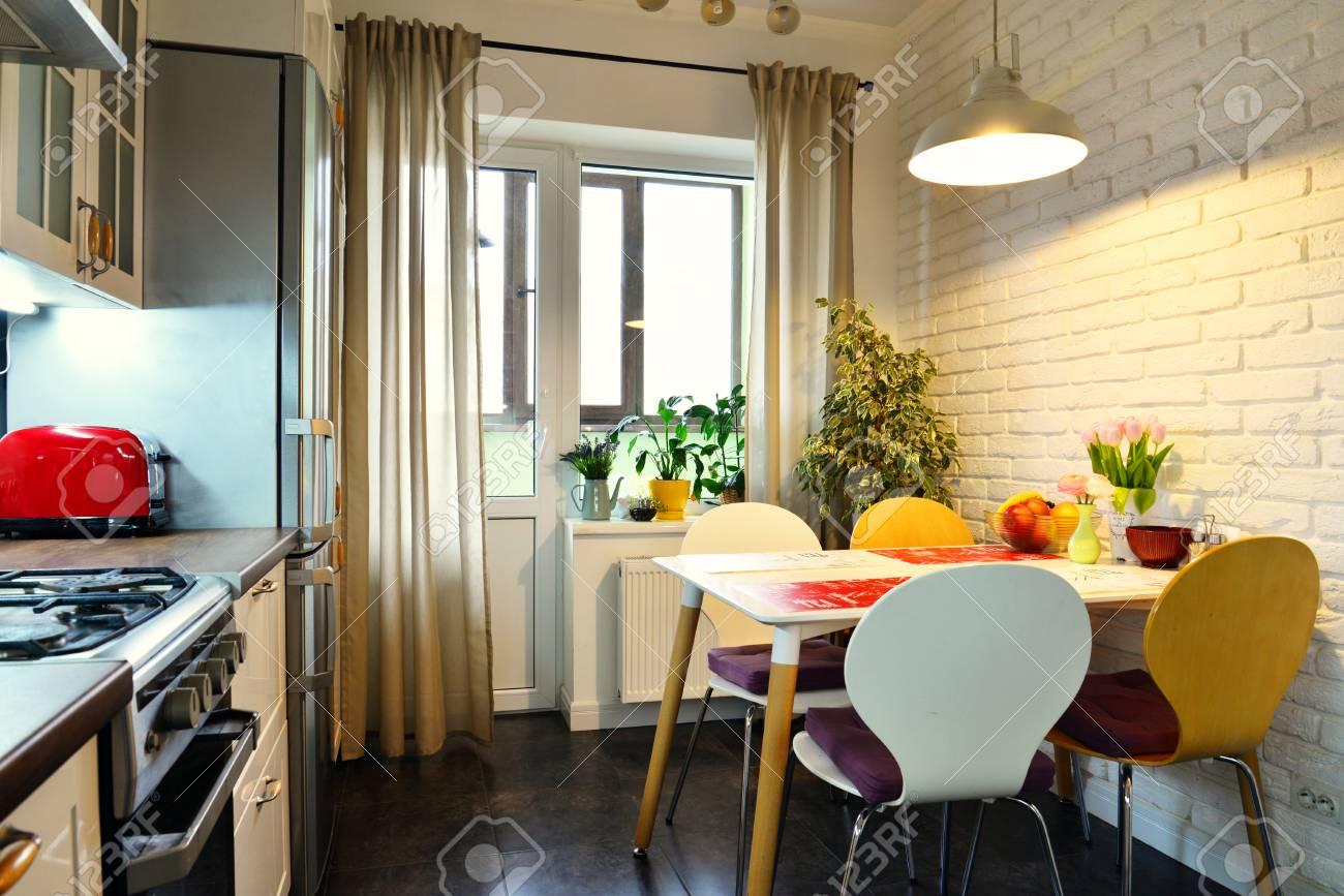Intérieur de la cuisine en style scandinave avec meuble blanc et table à  manger