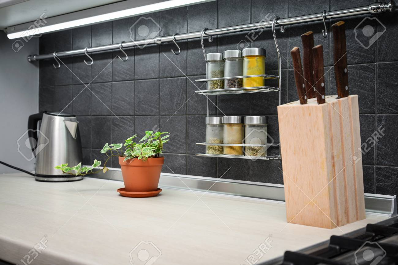 Kitchen utensils and jars of spices in hanging shelf in modern..