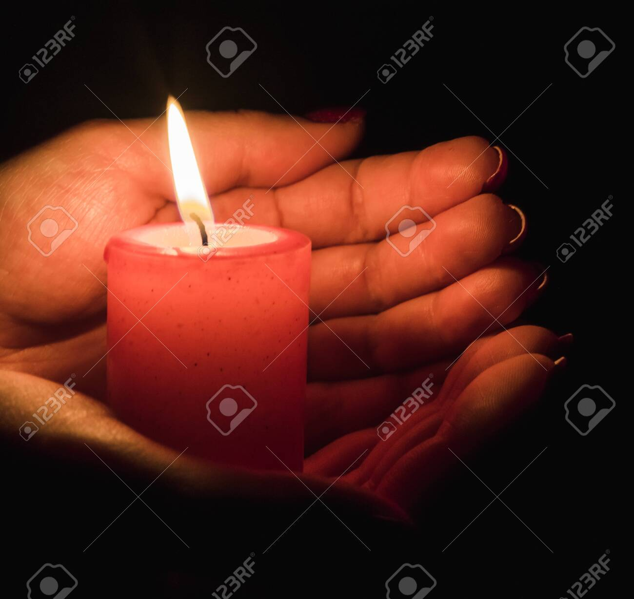 Female hands holding a burning candle in the dark - 137930335