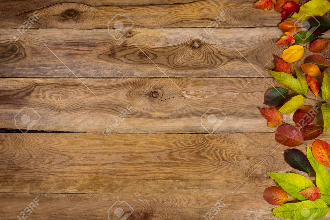 Happy Thanksgiving Greeting With Colorful Autumn Leaves On The Right Side Of Rustic Wooden Table