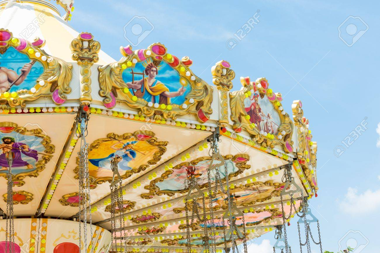 top section of marry go round amusement park ride with clear blue sky - 19612077