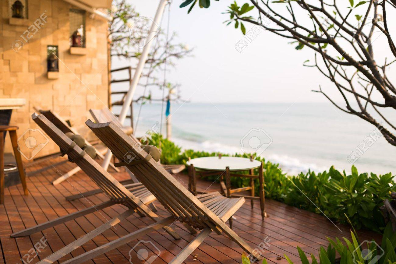 Wooden chairs on balcony of hotel by the beach - 22176992