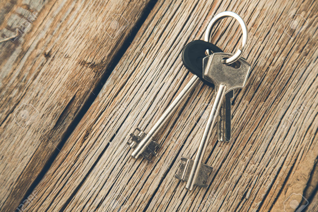different keys on the wooden desk background - 147365942