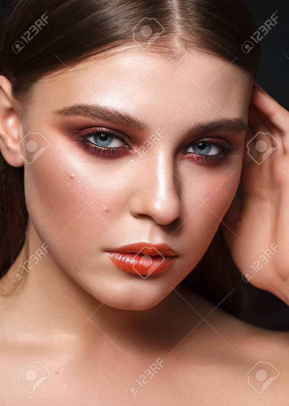 Perfect model with the professional colorful makeup, perfect skin and red smoky eyes. Closeup portrait. - 133209077