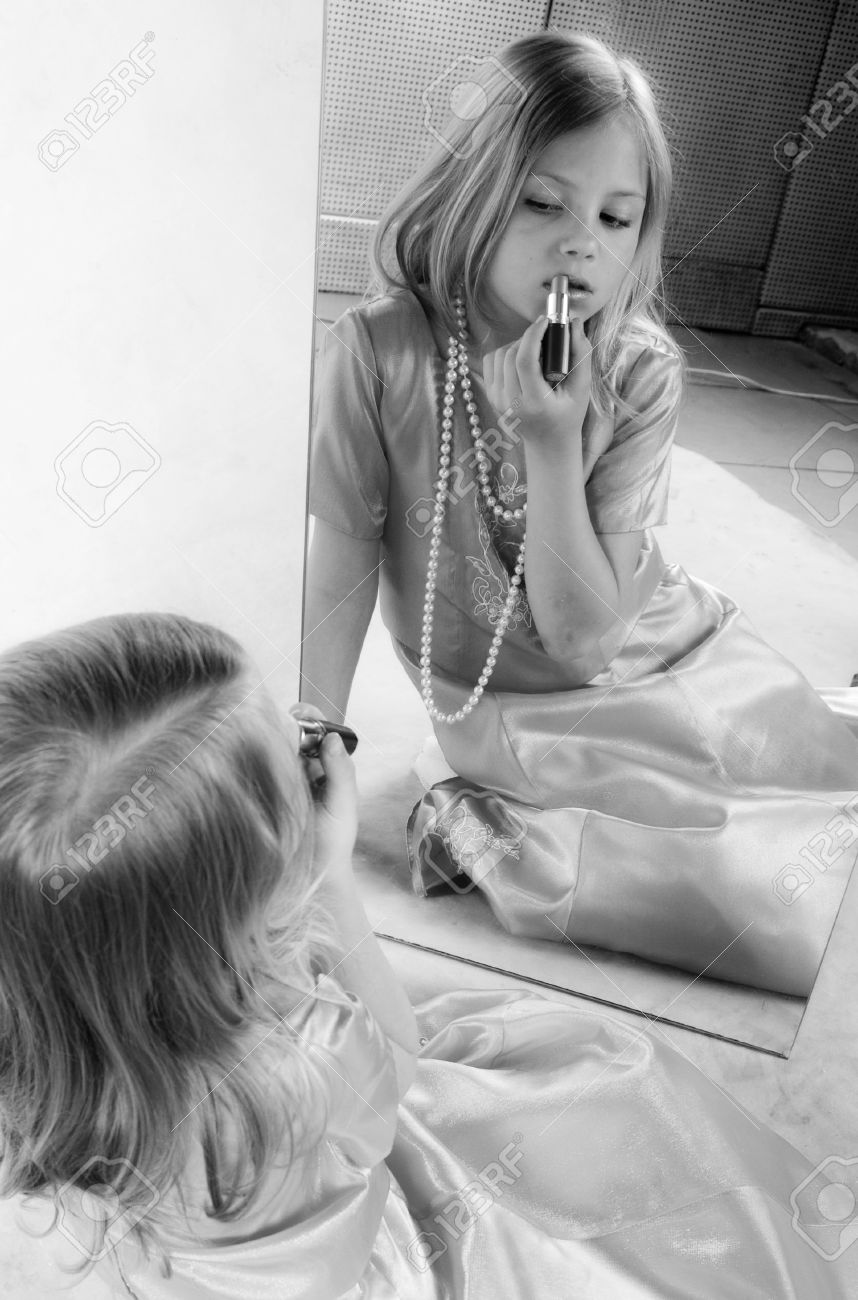 black child looking in mirror. little girl rouge lips and looking at mirror, studio photo, black white portrait child in mirror g