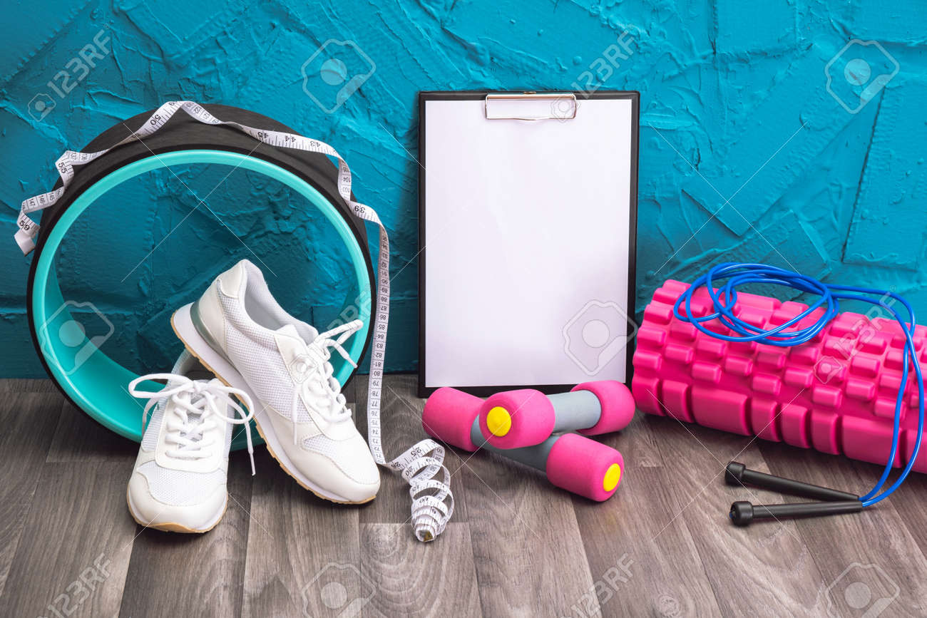 workout at home - white sneakers, dumbbells, jump rope, measurement tape, note board and massage roller, close-up and blue background - 169056391