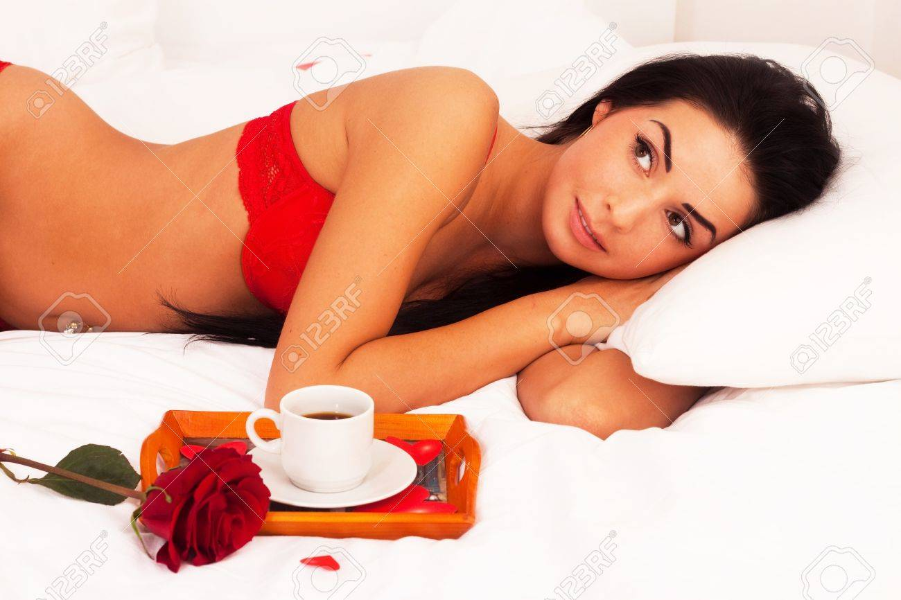 in love with a beautiful young girl lying in bed with gifts, cards, hearts, coffee, roses. Feast day of St. Valentine Stock Photo - 8645462
