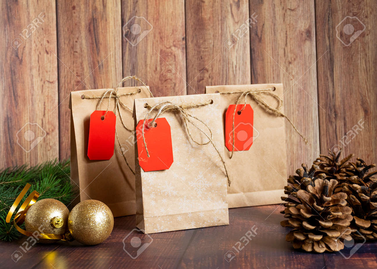 Vintage handmade gift boxes made of kraft paper on a wooden background in the Christmas style, decorated with golden Christmas balls, cones, fir branch. Christmas, New Year, winter holiday. Kraft package, holiday concept, top view, flat lay. Mocap. - 135332122